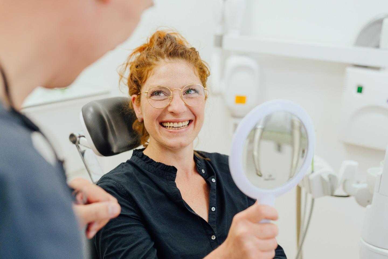 Nils Marckardt mit lächelnder Patientin, die in den Spiegel schaut