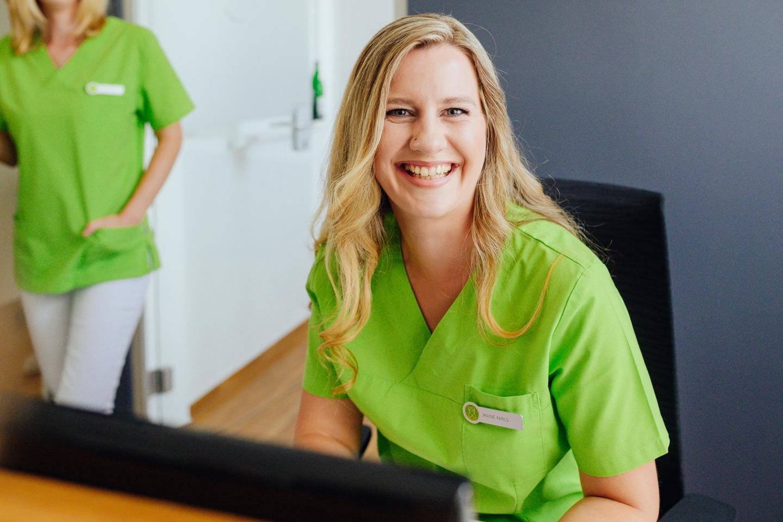 Zahnmedizinische Fachangestellte begrüsst lächelnd die Patienten