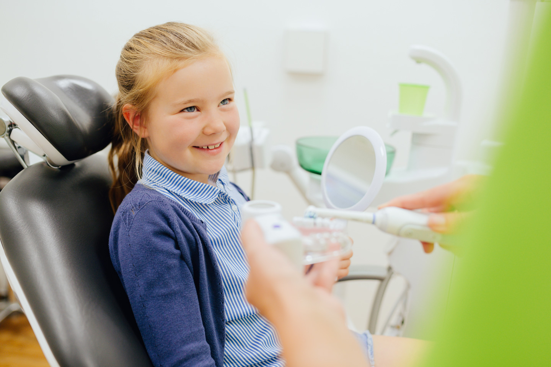 Zahnmedizinische Prophylaxeassistentin erklärt einem Kind die Zahnpflege